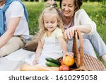 Small photo of Mother and her little daughter rummage in a picnic basket outside in the park.