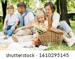 Small photo of Mother and her little daughter rummage in a picnic basket.