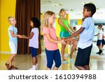 Small photo of Group of cheerful positive smiling children practicing vigorous jive movements in dance class with female coach