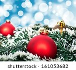 Red and golden christmas ornament ball against blue bokeh background - stock photo