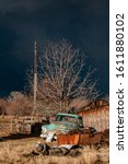 Antique warm front lit rusty light blue pickup truck sits near a rusty junk pile near an aged wooden structure under the stormy dark sky with a leafless tree overhead - stock photo