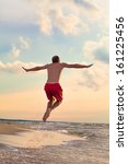 happy man jumping on the beach  | Shutterstock . vector #161225456