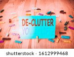 Small photo of Word writing text De Clutter Your Life. Business concept for remove unnecessary items from untidy or overcrowded places Colored clothespin papers empty reminder wooden floor background office.