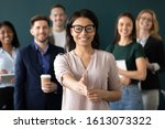 Small photo of Mixed race woman sales manager stretch out hand introduces herself greeting shake hands client smiling look at camera pose indoors with diverse teammates. HR, job interview, business etiquette concept