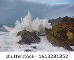 A Large Wave Crashes Against...