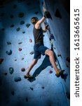Small photo of Teenage Boy Training Climbing On Indoor Climbing Wall