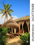 Small photo of Dried Palm Leaves Thatched Roof Pavilion and Sunshade on the Tropical Beach