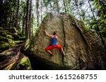 girl climbing hard boulder problem in forest. Sport climbing, bouldering.