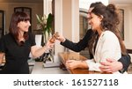 Stock photo happy young couple at hotel reception receiving the key of the room 161527118