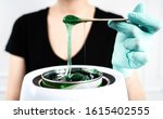 Small photo of The concept of depilation and beauty is sugar paste or hair removal wax. Preparation of green wax for sugaring. Close-up sugar paste or wax honey for hair removing with wooden waxing spatula sticks.