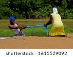 Small photo of Mankpan, Ghana - December 15, 2019: Wringing the clothes in Ghana. Two women at a rivercouse twist and pull a cloth to wring it.
