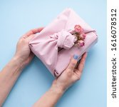 Small photo of Female hands holding a holiday gift packed fabric in the manner of Furoshiki on a fashionable blue background.