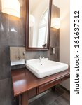 White classy bath sink on a wooden furniture - stock photo