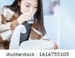 Small photo of Young Asian female gargle in dental room