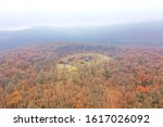 Wallowing in animals on the hilltop, autumn forest aerial stock photo.