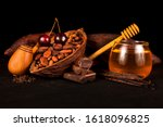 Small photo of Cocoa pod and cocoa beans, cherry, bourbon vanilla pods, chocolate, tobacco pipe and glass jar of honey. Still life on a black background.