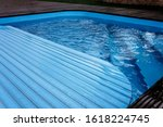 Small photo of Automatic swimming pool covering system, safely protect children and pets from accidental contact with water, home and cottage equipment, copyspace, place for text, outdoor exterior