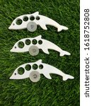 Small photo of Arrangements small Conventional pill cutters use a �V' shaped trough in a one size fits all design that can give a poor and inconsistent cut. Isolated on fresh green grass back ground