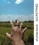 Small photo of EAST JAVA,INDONESIA - SEPTEMBER 2 2018: a finger that will seize the beautiful rice fields