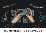 Small photo of Old woman shuffle tarot cards above other tarot cards. Old wrinkeld hands. Occult fortune telling concept