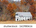 An Old White Barn Is Backed By...