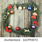 Vintage Christmas background with wreath balls and decorations over wooden table - stock photo