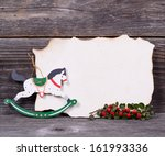 Christmas background with empty paper and wooden horse decoration and berries - stock photo
