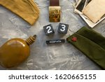 Small photo of Flask, cap, soldier belt with a five-pointed star with a hammer and sickle. old photographs of the war years and a wooden calendar with the date February 23. Fatherland defender day. Text in Russian