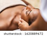 Small photo of Beautiful african woman getting face massage in beauty spa. Black girl with closed eyes relaxing in outdoor spa while getting head massage. Serene woman relaxing outdoor in a beauty center.