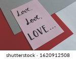 """Small photo of """"Love love love"""" handwritten on pink paper about art composition on colored papers gray and red - perspective"""