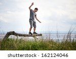 young adult balancing on a dead ... | Shutterstock . vector #162124046