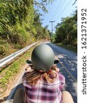 A shot from behind of western lady wearing matte green helmet driving motorbike on the roadon te mountain in Asia. Refer to freedom of woman - stock photo