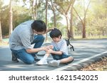 Small photo of Young asian father of dad calms son that fell from the bike and he get injury on knee and leg while have weekend leisure in public park,accident can happen everywhere and every time.