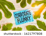 Small photo of Conceptual hand writing showing Corporate Flunky. Business photo showcasing someone who works obediently for another demonstrating in company Leaves surrounding notepaper above a classic wooden table.