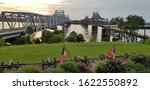 Two bridges crossing the Mississippi River contrasting old and new, railroad and highway, and train and road in Vicksburg, Mississippi with the United States and State of Mississippi flag flying.