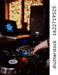 Small photo of DJ Spinning, Mixing, and Scratching in a Night Club, Hands of dj tweak various track controls on dj