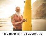 Tattooed Senior Surfer Holding...