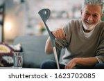 Senior Man With Crutch Sitting...
