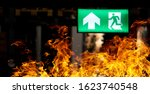 Small photo of Hot flame fire and green fire escape sign hang on the ceiling in the Warehouse at night. The concept of fire escape training and preparation for evacuation