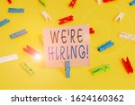 Small photo of Text sign showing We Re Hiring. Conceptual photo recently employ someone or pay him to do particular job Colored clothespin papers empty reminder yellow floor background office.