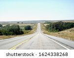 An empty road or highway with no other cars, trucks or travelers in Wyoming, United States of America.