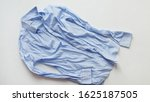 Small photo of Blue cotton wrinkled and rumpled shirt on white. Washed shirt after tumble dryer
