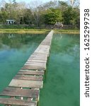 Small photo of old wooden gangplank bridge over shallow water heading towards an island with topical trees and some small buildings on.