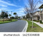 Small photo of Orlando, FL/USA-1/23/20: A curved sidewalk and street next to a lake that is a walking path in front of homes in Laureate Park Lake Nona an Orlando, Florida neighborhood.