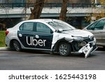 Small photo of Minsk, Belarus - Nov 2019. Damaged car of Uber taxi service at the parked zone after car accident on the road. Wrecked taxi car after a head-on collision in a parking lot