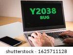 Small photo of Man hands typing on a laptop in text code. Problem Y2038 concept, also called, year 2038 bug or Unix Y2K. On january 19, 2038 many computers will encounter a date-related bug