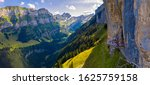 Aerial panorama of the Swiss Alps and a historic mountain restaurant under the Ascher cliff located in the Appenzell region in Switzerland