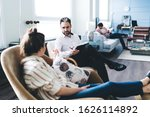 Small photo of Side view of trusting woman in casual outfit speaking to friendly understanding man in shirt with clipboard while sitting in cozy chair in light office