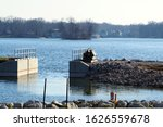 Small photo of Coventry Township, Ohio / USA = 1/15/2020: Working on damn reconstruction on East Reservoir in the Portage lakes on near North Turkeyfoot road and Portage lakes dr. Showing Cat Swamp in foreground