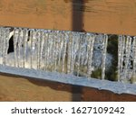 Small photo of close up detail photo of clear shimmering cold icicles hanging from contrasting brown wood fence rails after a freezing rain storm with sunshine reflecting through them